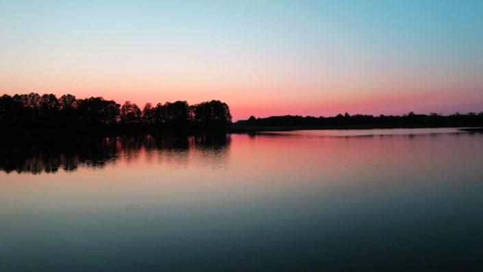 Pokoje nad Jeziorem Mazury   Jezioro - zachód słońca za półwyspem, a niebo jest przy tym różowe. Dom nad Zatoką
