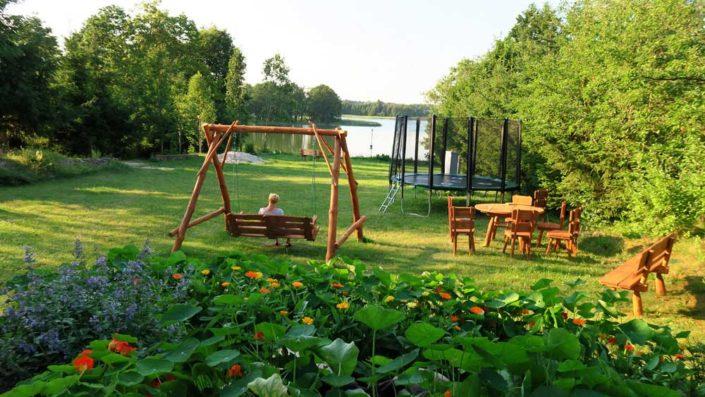 Pokoje nad Jeziorem Mazury | Teren rekreacyjny - na łące huśtawka, ławki, trampolina, stół, krzesła, a w oddali jezioro. Dom nad Zatoką