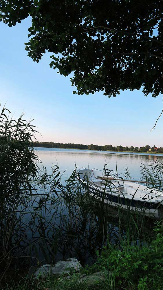 Pokoje nad Jeziorem Mazury   Jezioro - widok na łódkę zacumowaną wśród trzcin i zatokę. Dom nad Zatoką