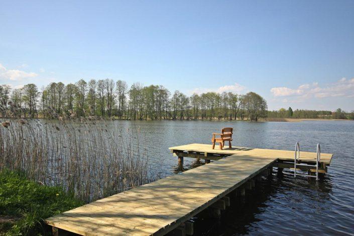 Pokoje nad Jeziorem Mazury | Pomost z ławką i drabinką oraz trzciny, widok na półwysep. Dom nad Zatoką