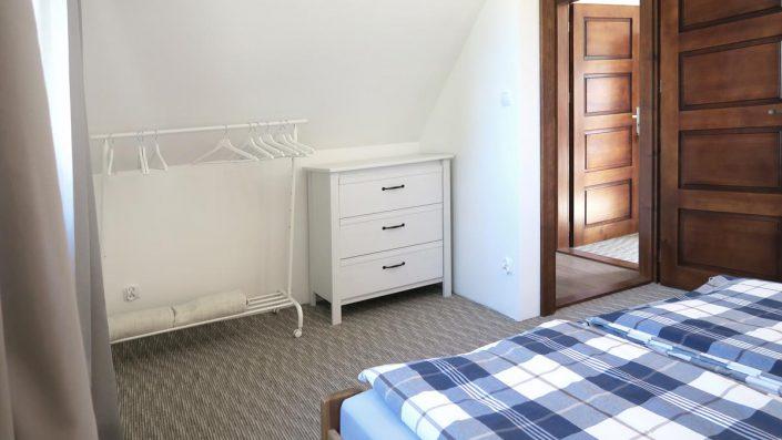 Pokoje nad Jeziorem Mazury | Apartament nr 6 pokój z łożem małżeńskim, widok na drzwi, komodę i wieszaki. Dom nad Zatoką