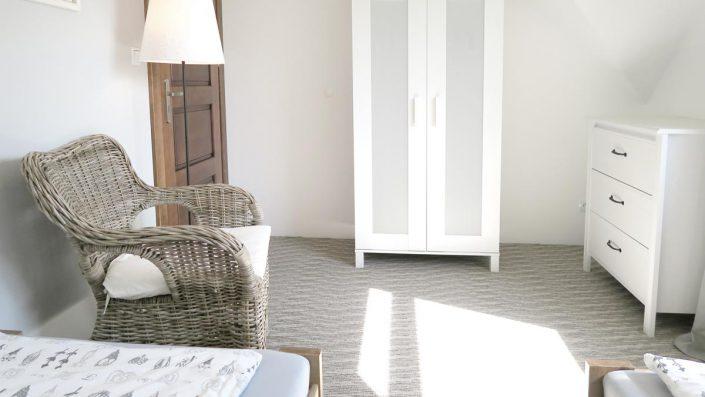 Pokoje nad Jeziorem Mazury | Apartament nr 6 pokój z dwoma łóżkami widok na drzwi, fotel, szafę, komodę i lampę do czytania. Dom nad Zatoką