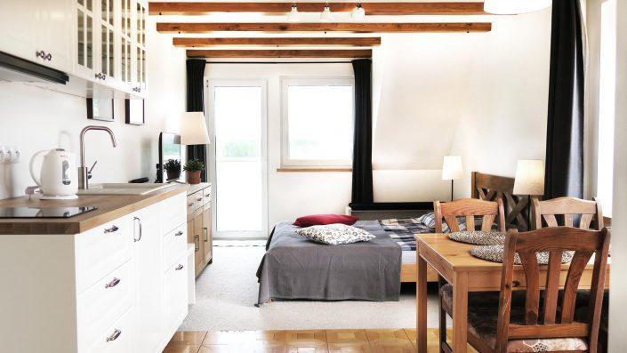 Pokoje nad Jeziorem Mazury | Studio nr 3 duży pokój z aneksem kuchennym widok w stronę drzwi na balkon od strony jeziora. Dom nad Zatoką